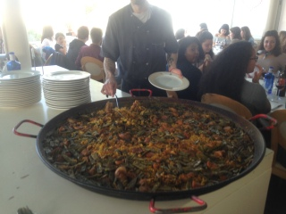 A camarero prepares a plate from one of several humongous pans of paella